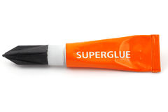 Orange plastic tube labeled superglue Royalty Free Stock Photos