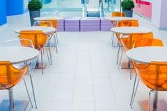Orange Plastikstühle und eine weiße Tabelle auf Gastronomiebereich Lizenzfreies Stockbild