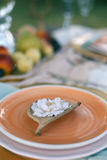 Orange plate decorated with a beautiful white flower against the background of a served table. Focus on the flower. Closeup photo Royalty Free Stock Image