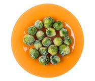 Orange plate with frozen brussels sprouts isolated on white Stock Images