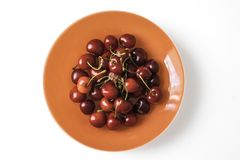 Orange plate full of sweet red cherries Royalty Free Stock Images