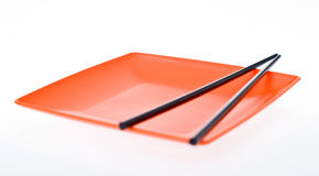 Orange plate with two chinesse stick Stock Images