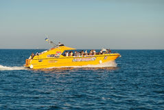 Orange pleasure boat with people on the Black Sea Royalty Free Stock Photography