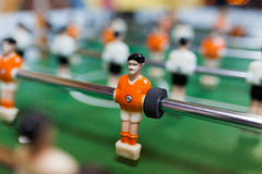 Orange pleyer in table football. A withe and orange football player from table game royalty free stock photography