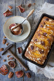 Orange plumcake with pecan walnuts on mold on rustic wooden table with dried orange Royalty Free Stock Photo