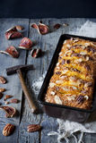 Orange plumcake with pecan walnuts on mold on rustic wooden table with dried orange slices Stock Photography