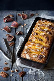 Orange plumcake with pecan walnuts on mold on rustic wooden table with dried orange slices Royalty Free Stock Image