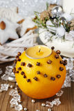 Orange pomander ball with candle decorated with cloves Stock Image