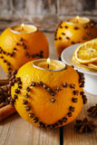 Orange pomander ball with candle decorated with cloves in heart Royalty Free Stock Photos