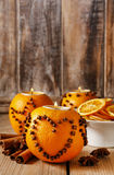 Orange pomander ball with candle decorated with cloves in heart Stock Photos