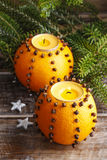 Orange pomander ball with candle. Fir branches in the background Royalty Free Stock Image