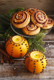 Orange pomander balls with candles and cinnamon rolls Stock Photo
