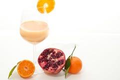 Orange and pomegranate smoothie. Healthy orange, pomegranate and kefir yogurt smoothie milkshake. Served with fresh sliced orange and whole pomegranate. Isolated Stock Image