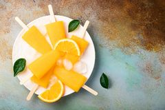 Orange popsicles with juice on a rusty blue bacground. Ice pops, flat lay, top view with copy space royalty free stock photo