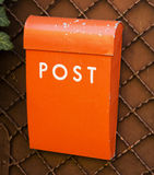 Orange post box on a wall Stock Images