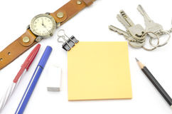Orange post it with keys watch and bulldog clip and black pencil Royalty Free Stock Photo