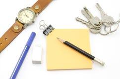 Orange Post-It mit Schlüsseln Uhr und Bulldoggenclip und schwarzer Bleistift Stockfotos
