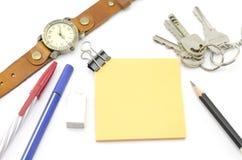 Orange Post-It mit Schlüsseln Uhr und Bulldoggenclip und schwarzer Bleistift Lizenzfreies Stockfoto