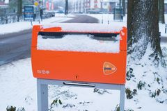 Orange postbox i snö royaltyfri bild
