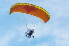 Orange powered tandem para glider flying Royalty Free Stock Image