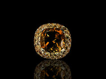 Orange precious gem. An orange precious gem on a black background with reflection Royalty Free Stock Photo