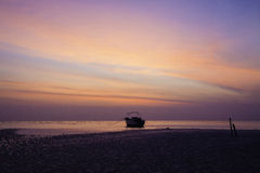 Orange predawn skies and a stranded lone boat. The low tide of predawn and dead calm sea has immobilised this lone motor boat anchored near shoreline while the Stock Photo