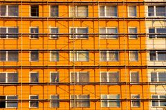 Orange prefab. Scaffolding on a block of flats Royalty Free Stock Photo