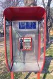 Orange public telephone on metallic background Stock Images