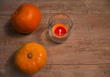 Orange pumkins with colorful candle in the glass on the wooden boards. royalty free stock photography