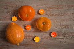 Orange pumkins with colorful candles on the wooden boards. royalty free stock image