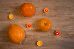Orange pumkins with colorful candles on the wooden boards. royalty free stock photos
