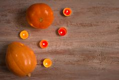 Orange pumkins with colorful candles on the wooden boards. stock photo