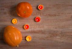 Orange pumkins med färgrika stearinljus på träbrädena arkivfoto