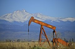 Orange Pump Jack Oil Well and Longs Peak stock photo