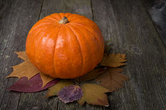 Orange pumpkin and autumn leaves on the old wooden background Royalty Free Stock Photography