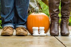 Orange pumpkin with baby shoes and parents shoes standing next t. Female baby shoes in front of a pumpkin symbolizing a baby born in the fall season with the royalty free stock images