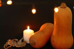Orange pumpkin with burning candle on a black background with a garland. royalty free stock images
