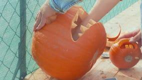 Orange pumpkin carved for Halloween celebration by man hands