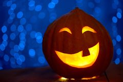 Orange pumpkin prepared for Halloween yellow lights on background. Royalty Free Stock Photos