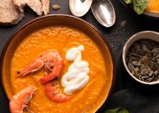 Orange pumpkin soup with shrimps stock image