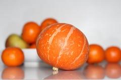 Orange pumpkin on the table. On the table is an orange pumpkin, behind it are orange mandarins stock photography