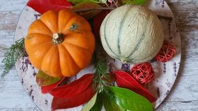 Orange pumpkins and colorful autumn leaves. Vibrant orange pumpkins and colorful autumn leaves on old wooden background Stock Photo