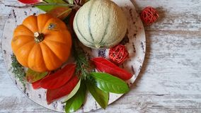 Orange pumpkins and colorful autumn leaves. Vibrant orange pumpkins and colorful autumn leaves on old wooden background Stock Image