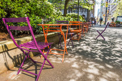 Orange and purple colored chairs in with people walking in Vancouver, Canada Royalty Free Stock Image