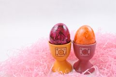 Orange and purple Easter eggs in eggcups. Two Easter eggs, colored on orange and purple by artificial dyes, in eggcups and pink artificial hay, on white Royalty Free Stock Images