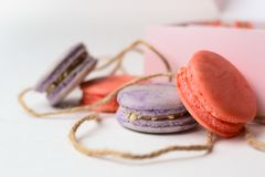 Orange purple macaroons cakes next to the packaging with ropes stock photo