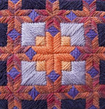 Orange and Purple Needlepoint Detail. Close up of a needlepoint pillow stitched by Cathy Decker in Persian wool and chenille yarn in oranges and purples Stock Photo