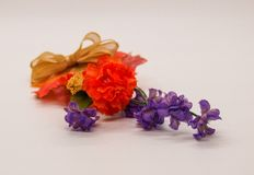 Autumn Silk Flowers and Bow. Orange and purple silk flowers tied together with a bow to create a mini autumn bouquet stock photos