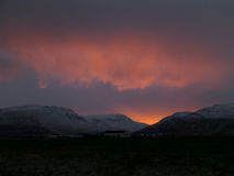 Orange and purple sunset after glow over the snow capped mountain range Stock Image