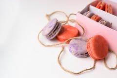 Orange purpurrote Makronen backt nahe bei der Verpackung mit Seilen zusammen lizenzfreies stockfoto